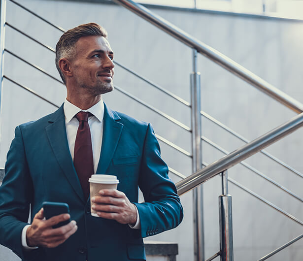 Stoic business man holding cell phone and coffee