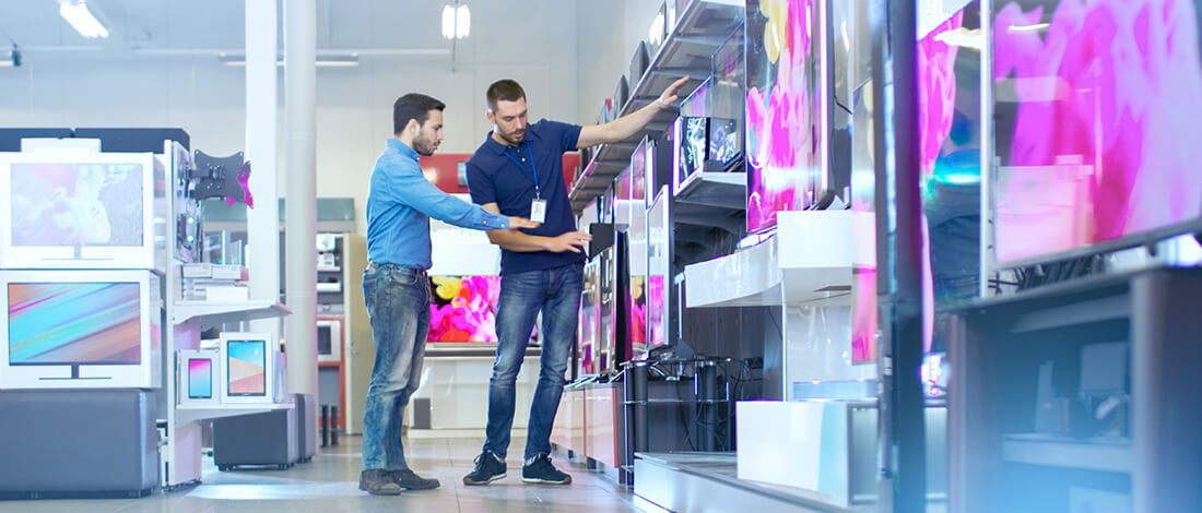retail worker showing flat screens to customer
